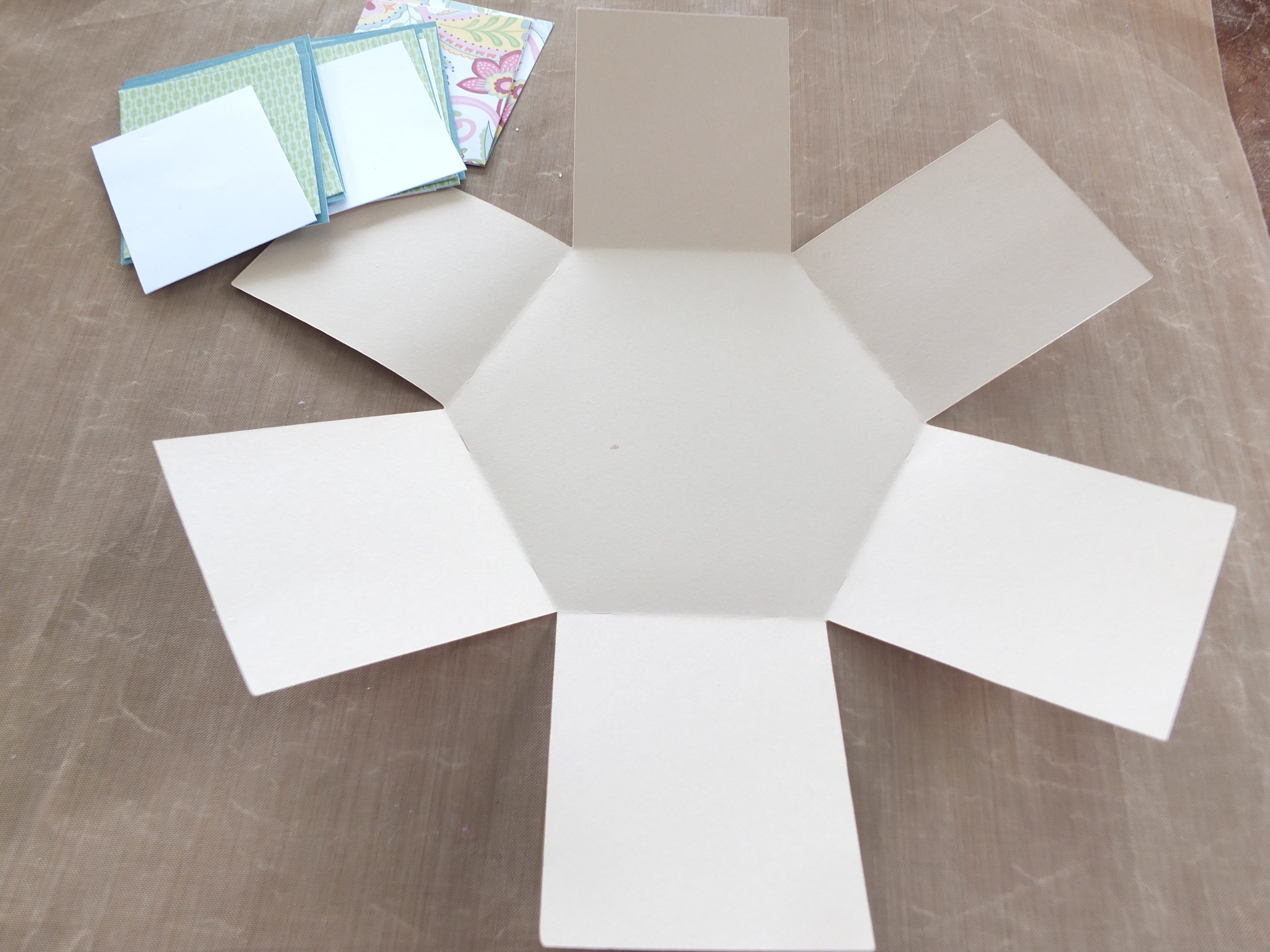 Base shape of exploding box with papers and cardstock cut ready to adhere to bas